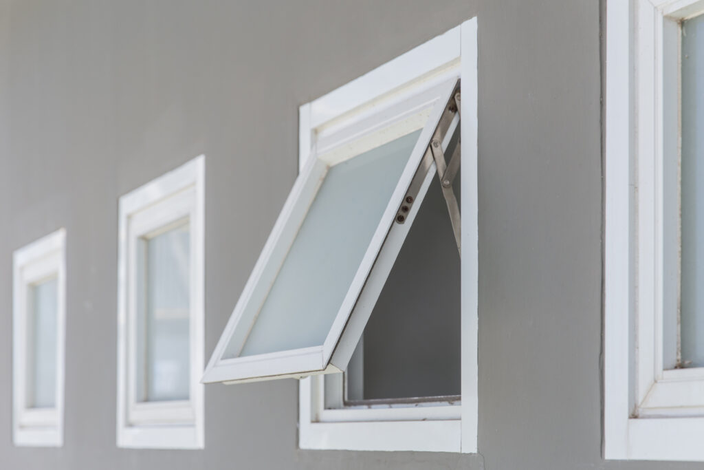 Opened awning window on a gray building